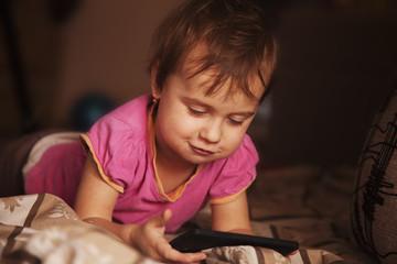 Little beautiful  girl with her smart phone (Development, educat