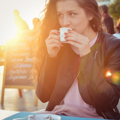 Woman sitting in restaurant cafe table on sunny background outdoors