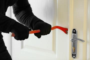 Male thief opening door with scrap