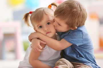 Cute little boy hugging sister at home