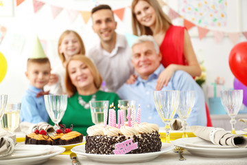 Birthday cake on table with happy family on background
