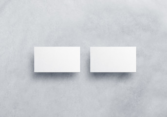 Blank white business card mockups isolated on grey textured background. Front and back side namecard design mock up presentation. Empty horizontal visiting paper sheets template with shadows.