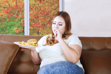 Fat woman eating junk food on the couch