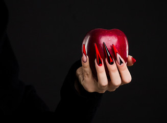 Hands with scary nails manicure holding red apple , isolated on black background