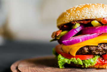Burger on a wooden table against black background. Selective focus