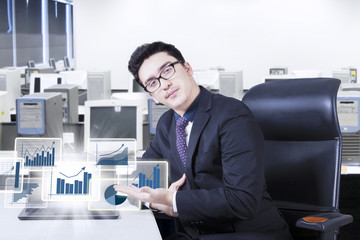 Handsome man shows financial graph