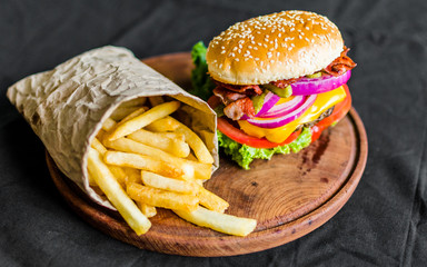 Burger and french fries on a wooden table against black background. Selective focus