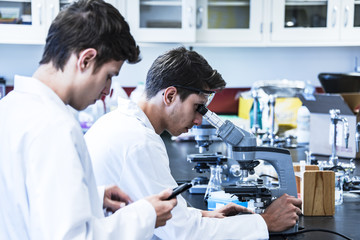 Science research project conducting with two young male scientific researchers in laboratory