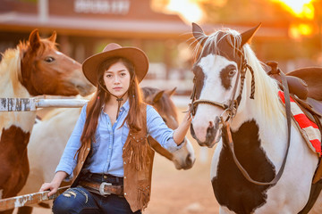 Beautiful womam sensuality elegance woman cowgirl on during sunset, riding a horse. Clothed blue jeans, brown leather jacket and hat. Has slim sport body. People and animals. Equestrian. vintage style