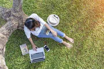 girl enjoy music with over headphone under the tree and fool around with online songs players