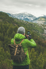 Young man traveller wearing green jacket making photo of slopes and mountains with snowy peaks in Dim Cay district of Alanya on gloomy day, Antalya province, Mediterranean Turkey