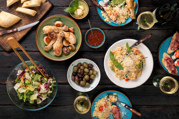 Variety of Italian food with wine on dark wooden table