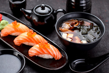 Japanese cuisine. Salmon sushi nigiri and miso soup on black plate a dark table.