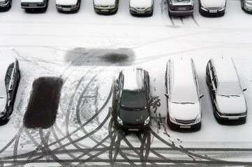 Ground parking cars after snowfall, view from above. Automobiles covered with snow, the traces of wheels and legs.