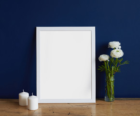 Empty white frame mockup for design presentation, bouquet of flowers ranunculus and two white candles on a deep blue wall background and wooden table. Hipster romantic style concept, minimalism design