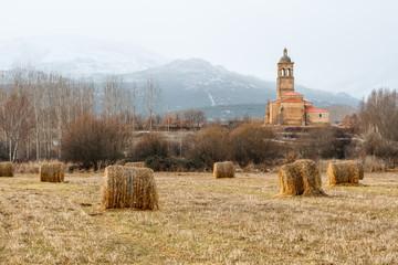 Campo con alpacas de paja e Iglesia del Cristo. Tabuyo del Monte, León, España.