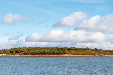 Presa de Valtabuyo. Embalse de Tabuyo del Monte, pinar y cielo azul con nubes.
