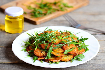 Sliced fried potatoes with arugula and spices on a white plate, a jar of olive oil, fork on wooden table. Homemade food recipe. Cottage fries. Closeup