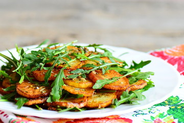 Fried sliced potato with fresh arugula and spices on a white plate on a wooden table. Combine fresh arugula mixture and hot potatoes. Tasty and healthy recipe. Closeup