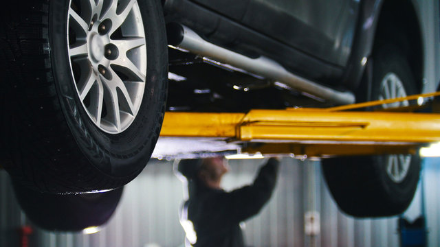 Car lifted in automobile service for fixing, worker repairs detail