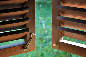 Semi-open dark wooden shutters with a metal hook lock close-up and view of the garden.
