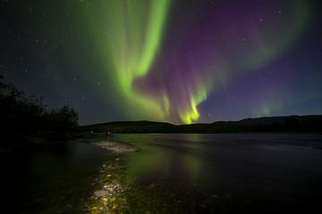 Aurora Borealis over the river. River Paypudyna. Polar Urals. Russia.