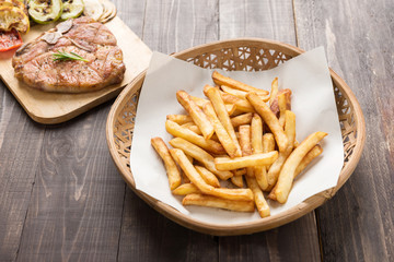Chips and grilled pork chop on the wooden background