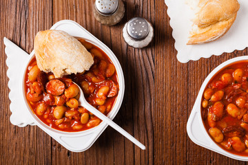 Baked beans in tomato sauce served in plastic cups.