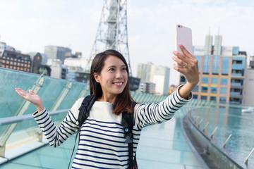 Woman taking seflie by mobile phone at Nagoya city