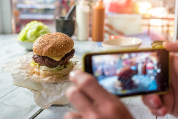 Burger on the table. Hands with phone photographing food. Share impressions about new cafe.
