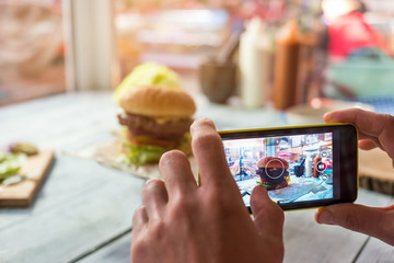 Cell phone photographing burger. Hamburger on table. Try food and share impressions.