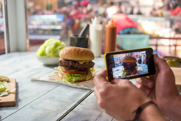 Photographing burger with cell phone. Hamburger on gray wooden table.
