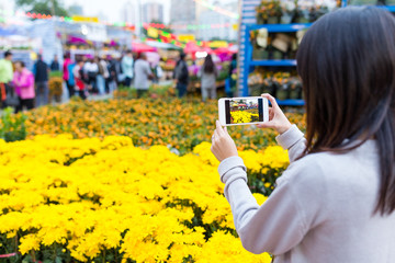 Woman taking photo with cellphone on Lunar new year flower marke