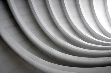 Architectural background. Modern white concrete arched composition in perspective. Semicircular shapes. The light in the end.