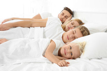 Cute happy family sleeping in bed at home