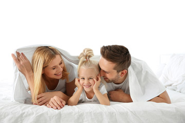 Cute little girl with parents lying on bed under white sheet