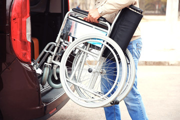 Man loading wheelchair of handicapped person