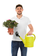 Male florist holding house plant and watering can on white background
