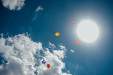 colorful balloons flying on blue sky with the sun