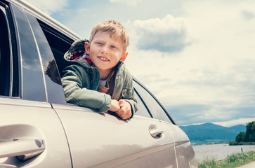 Boy looks out from car window