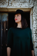Brunette girl in black with a stylish hat and a old wooden door
