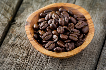 Coffee beans in wooden bowl on rustic background. Selective focus.