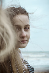 Beautiful teen girl with blue eyes at the beach in winter
