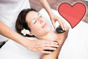 Composite image of hot stone massage session with a heart