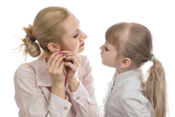 Mom tries earrings and daughter watching