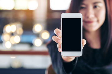 Mockup image of a beautiful woman holding and showing white mobile phone with blank black screen and smiley face in vintage cafe