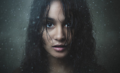 Girl staring through rainy glass