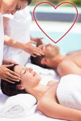 Composite image of a couple receiving a massage love heart
