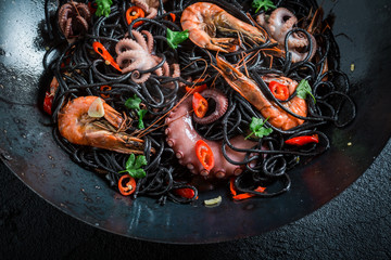 Tasty seafood black pasta with shrimp, octopus and parsley