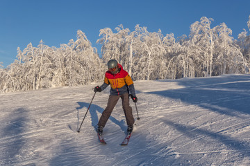 skier going down the slope at a ski resort